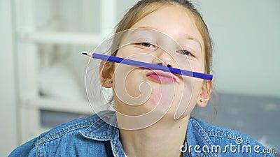 Schulmädchen, das Spaß hat und Gesichter mit farbigem Bleistift als Schnurrbart macht stock video