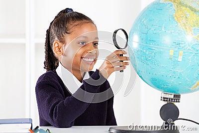 Schulmädchen, das Kugel betrachtet