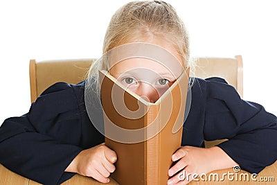 Schulmädchen versteckt sich hinter einem Buch