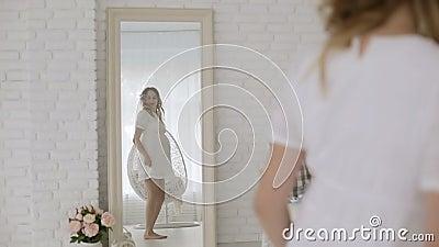 Schwangere Frau der Junge in einem weißen Kleid, das Spaßtanzen vor einem Spiegel hat stock video footage