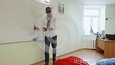 Schwarz-afrikanischer Englischlehrer erklärt Material in enger Klasse mit freundlicher Atmosphäre stock footage