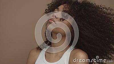 Schwarzes Modell mit dem enormen gelockten Haar, das Haar in der Zeitlupe rüttelnd von 60 fps sich bewegt stock video footage