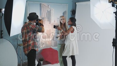 Schwarzes Modell mit Make-up-Künstler, die sich selbst machen, während Fotografen zusammen Fotos von ihnen stock footage