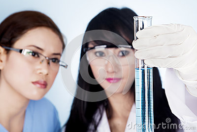 Scientific research team looking at clear solution