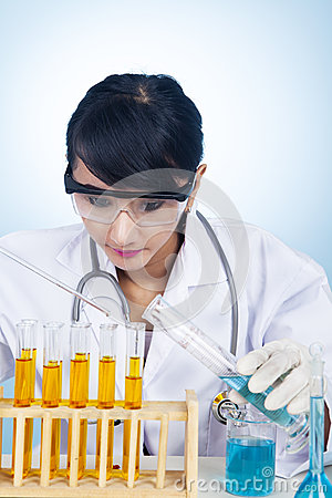 Scientist experimenting with yellow solutions