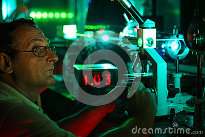 Scientist with glass demonstrate laser
