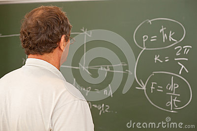 Scientist looking at formula on blackboard