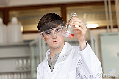 Scientist looking at a liquid in an flask