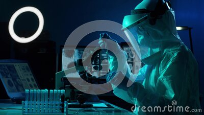 Scientist in protection suit and masks working in research lab using laboratory equipment: microscopes, test tubes stock footage
