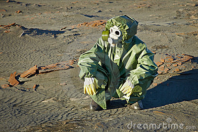 Scientist in protective suit sitting on slag
