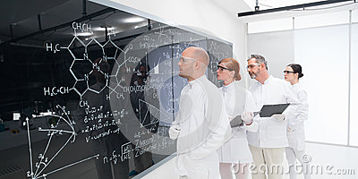 Scientists analyzing formulas in lab