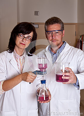 Scientists holding labware