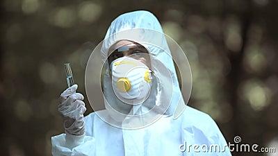 Scienziato femmina che detiene il tubo di prova con marca di radiazione, acqua infetta, ecologia stock footage