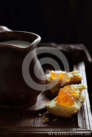 Free Scones With Orange Marmalade And A Jug Of Milk Against Backlight Royalty Free Stock Photo - 63361825