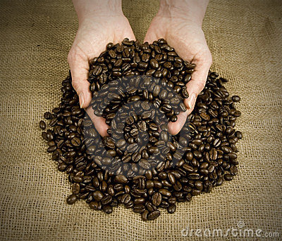 Scooping coffee beans with hands
