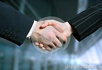 Scossa della mano di affari e un offi