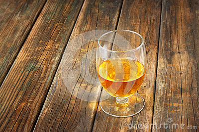 Scotch on wooden background with copyspace. An old and vintage table with glass of liquor .