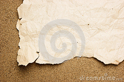 Scrap of old torn paper on sandy beach