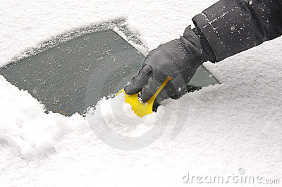 Scraping snow  from the car windscreen