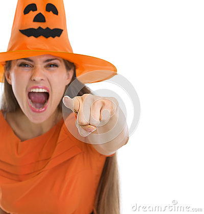 Screaming girl in Halloween hat pointing in camera