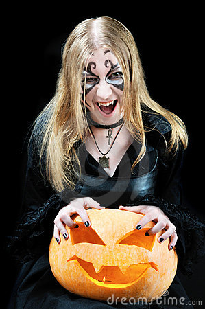Screaming vampire girl with a halloween pumpkin