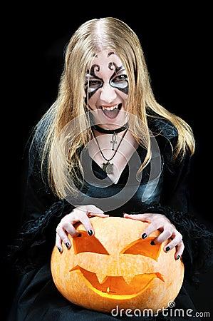 Screaming vampire girl with a halloween pumpkin