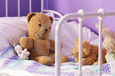Scruffy old teddy bears on a child s bed