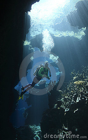 Scuba Diver in a cave with sunbeams