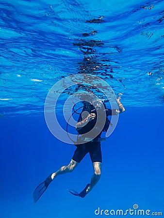 Scuba diver descends in blue water Editorial Stock Photo