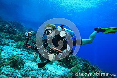 Scuba Diver explores coral reef with his camera