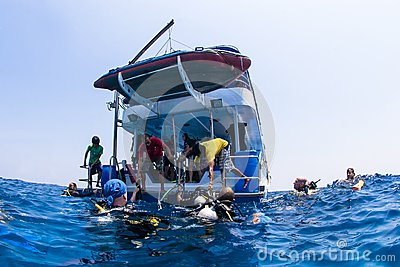 Scuba divers climbing back on dive boat on ocean Editorial Image