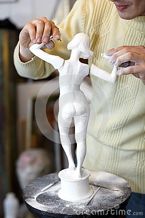 Sculptor attach arms to armless statuette.