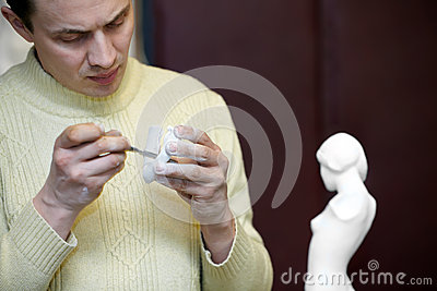 Sculptor files attentively fragment of sculpture