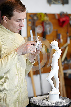 Sculptor works on fragment of sculpture