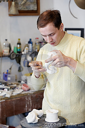 Sculptor works on fragment of statuette.