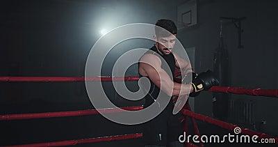 A scuola di palestra scura, nel mezzo di una boxe di un corpo di muscolo atletico ad anello, si fa una pausa dopo una partita di  stock footage