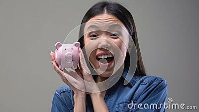 Señora asiática sonriente que sacude la hucha, extremidades del dinero, finanzas y el presupuesto de ahorro almacen de video