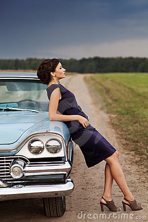 Señora hermosa que se coloca cerca del coche retro