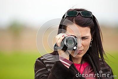 Señora joven que usa la cámara de vídeo al aire libre