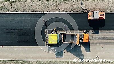 Se está colocando el asfalto en la carretera desde una vista superior Trabajadores de la construcción de carreteras almacen de video