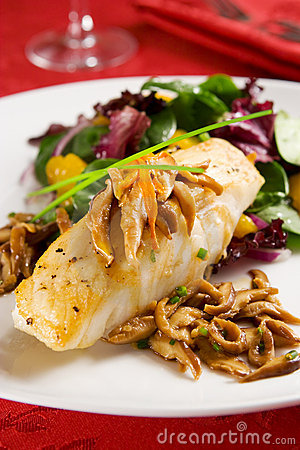 Pan seared Chilean sea bass with shiitake mushrooms and salad.