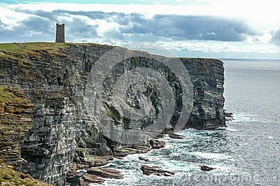 Sea cliffs with medieval tower in Orkeny Scotland