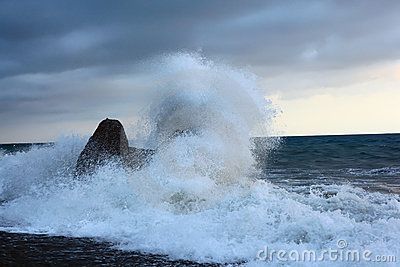 Sea coast with waves breaking about stone