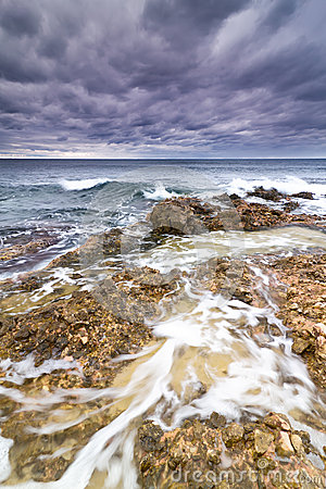 Sea, rocks and foam under a stormy sky.