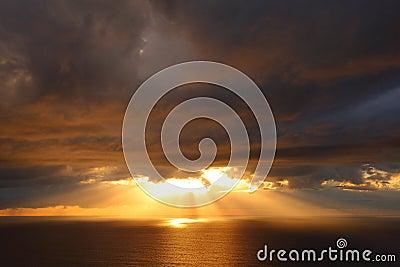 Sunbeams through storm clouds over ocean