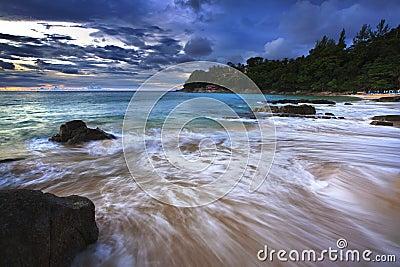 Sea waves lash line impact rock on the beach