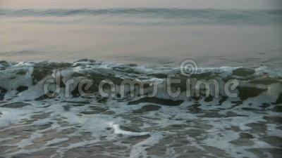 Sea waves wash the sand on the shore. Dim light in the evening. Dawn. Slowmotion stock video footage