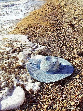 Sea and women`s hat on a shingle beach