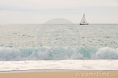 Sea, yacht, sky with wave and beach in foreground