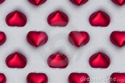 Seamless tile of red hearts in the snow